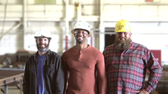 drei multi-ethnischen arbeiter tragen schutzhelme - bauarbeiterhelm stock-videos und b-roll-filmmaterial