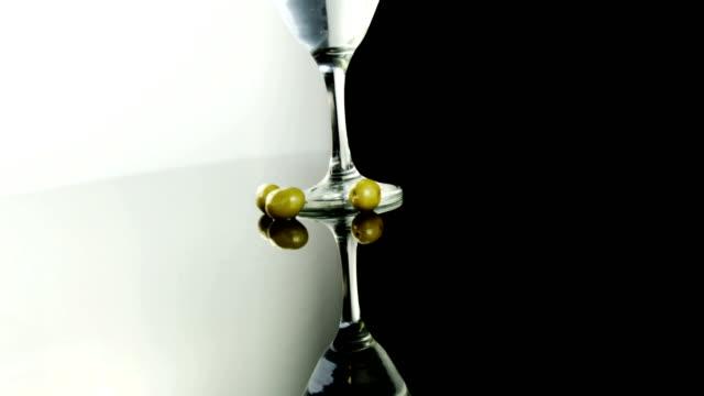 stockvideo's en b-roll-footage met drie olijven liggen naast een cocktailglas - martiniglas