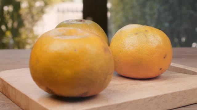 Three oranges on cutting board