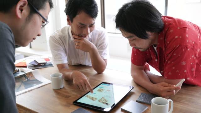 Three people adult men choosing material ビデオ