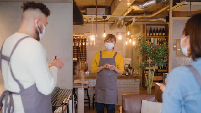 Three people covering their faces with protective face masks and having staff meeting in café before reopening