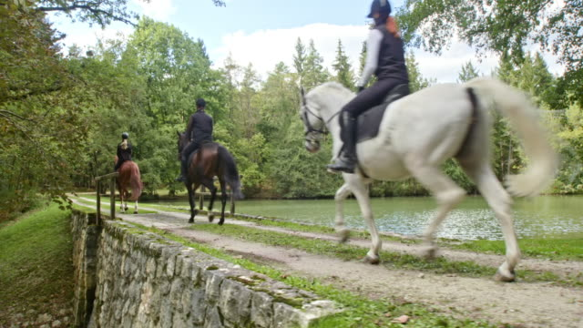 CS Three people riding horses over a small overflow dam