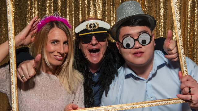 Three people wearing party props, holding a picture frame and taking fun photos in the photo booth at a party