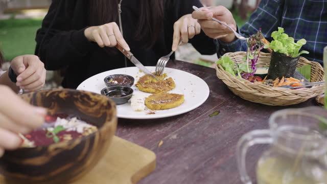 stockvideo's en b-roll-footage met drie persoon die verscheidenheid van veganistisch voedsel samen eten - drie personen