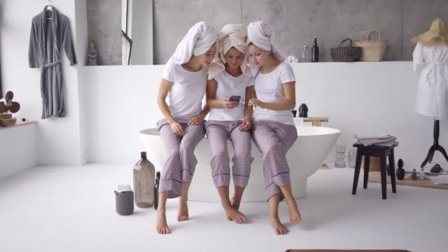 stockvideo's en b-roll-footage met drie positieve vrienden in dezelfde pyjama en handdoeken op hoofden tijd samen doorbrengen - cell phone toilet