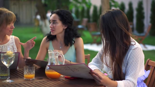 Three pretty girlfriends talking and reading menu in cafe outdoors in the park