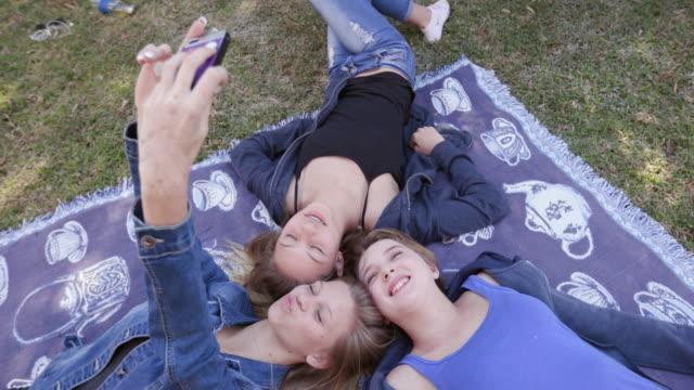 3 つのかなり若い 10 代の女の子は自分の携帯電話に selfies をとり、公園で楽しんで ビデオ