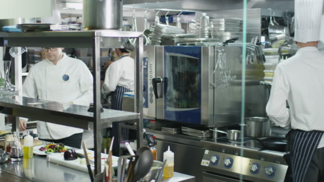 Three professional chefs in a commercial kitchen in a restaurant or hotel preparing food. video