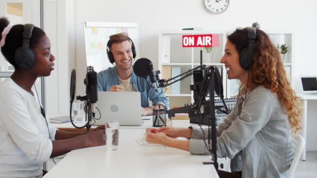vídeos de stock, filmes e b-roll de três hosts de rádio trabalhando no broadcast studio - podcast