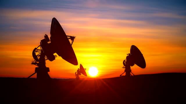 vídeos y material grabado en eventos de stock de tres radiotelescopios contra la puesta de sol escénica explorando el cielo nocturno - mástil