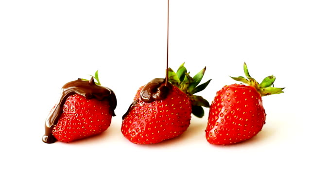 vídeos de stock e filmes b-roll de three ripe strawberries watered with melted chocolate on top, isolated on white background - strawberry
