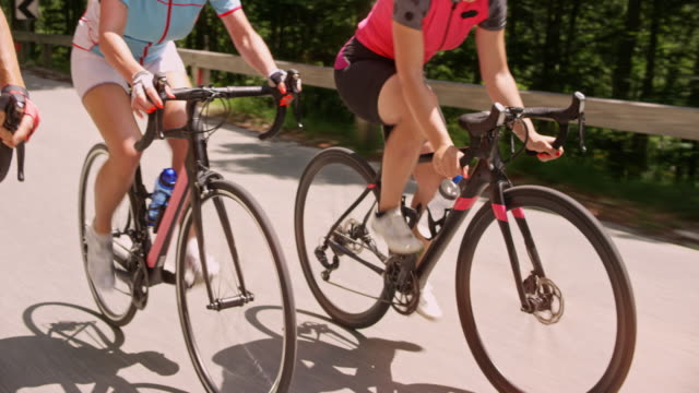 three road bicycles being ridden by female cyclists up a mountain road in sunshine - ciclismo su strada video stock e b–roll
