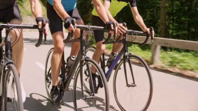 three road bicycles being ridden by male cyclists in sunshine - ciclismo su strada video stock e b–roll