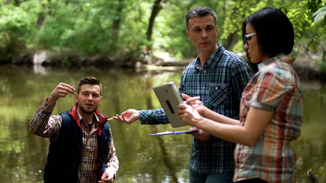 drei wissenschaftler erforschen wasser im see - medizinexamen stock-videos und b-roll-filmmaterial