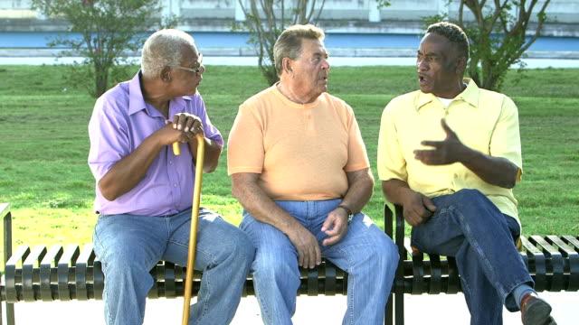 tre anziani seduti in panchina, che parlano - foro video stock e b–roll