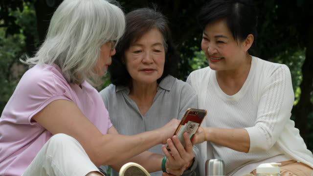 Three Senior Taiwanese Ladies Looking At Smartphone