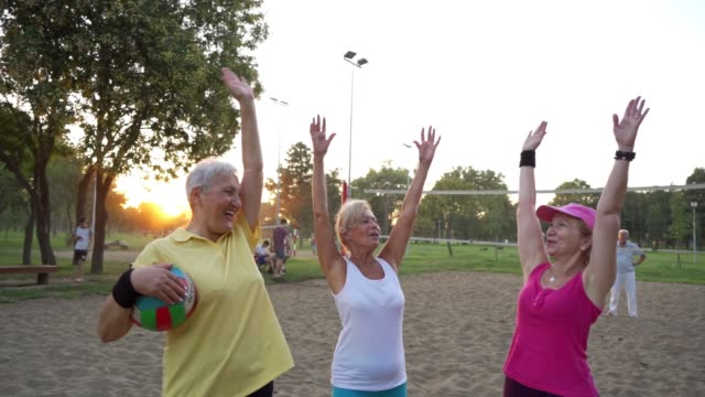 Three senior women celebrating after a score while playing a beach volleyball on sand Vital female senior friends enjoying a day at a park playing volleyball. volleyball sport stock videos & royalty-free footage