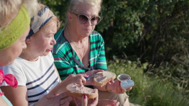 vídeos de stock, filmes e b-roll de três caminhantes mulheres sênior, tendo a pausa para o almoço - mulher passando creme