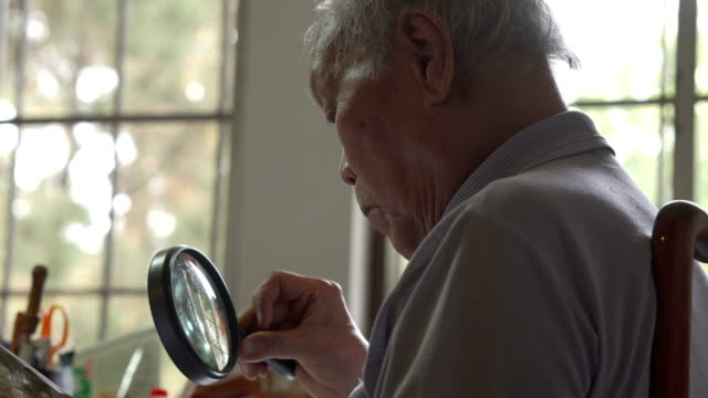 Three shots of Asian senior man using magnifier