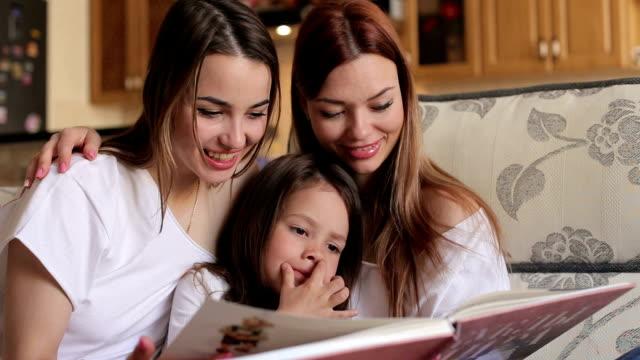 stockvideo's en b-roll-footage met drie zuster fotoalbum zittend op de bank kijken. - woman home magazine