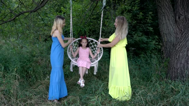 Three sisters of different ages play and have fun in nature on a Sunny day in colorful dresses. They rock the youngest daughter on the swing and smile. Fashion portrait. Close-up. 4K.