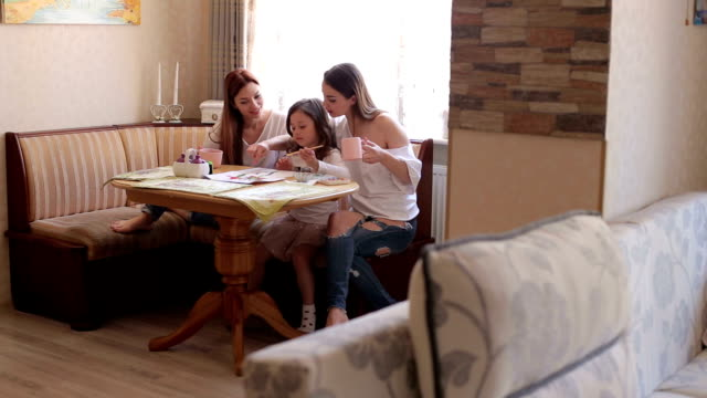 Three sisters paint at the table at home. video