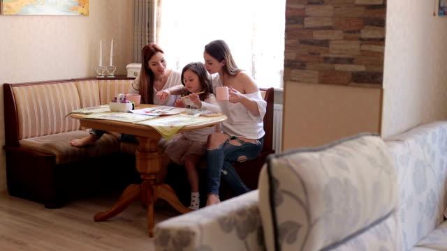 3 姉妹は、自宅のテーブルでペイントします。 ビデオ