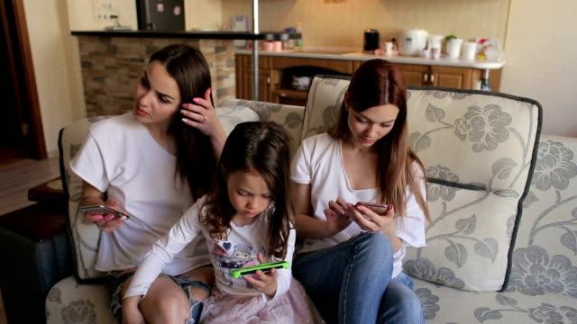 stockvideo's en b-roll-footage met drie zusters zittend op de bank thuis met telefoons - kids online abuse