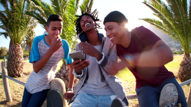 Three Skaters Sitting on Rail Looking at Smartphone video