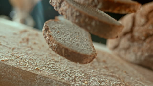 SLO MO LD Three slices of rye bread falling on the table