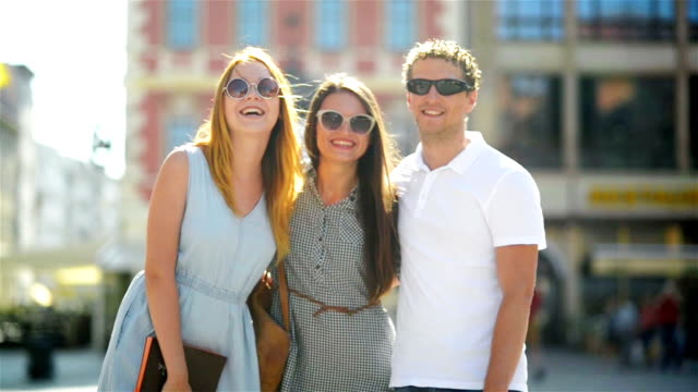 Three Smiling Friends in Fashionable Sunglasses are Looking at the Camera While Posing Outdoors on Urban Background video