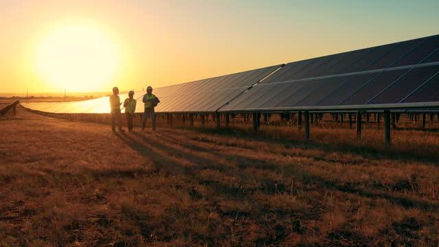 tre solenergi specialister går genom en sol park vid solnedgången. drönare skott - vitalitet bildbanksvideor och videomaterial från bakom kulisserna