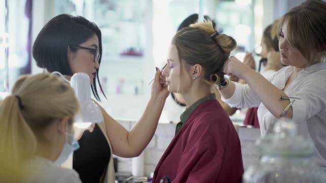 stockvideo's en b-roll-footage met drie specialisten modieuze afbeelding maken voor jonge dame in de beauty salon - toneelschmink