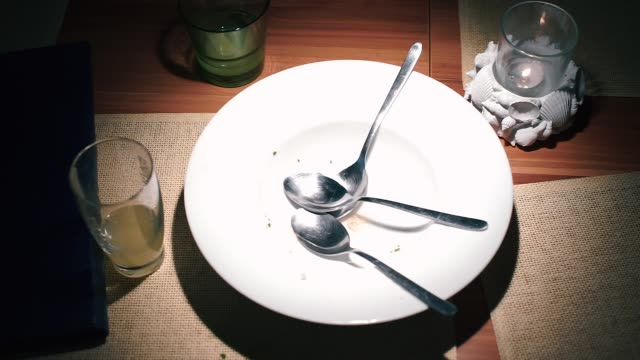 Three spoons in an empty plate on a table in a restaurant