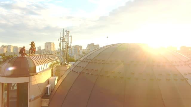 3 steeplejacks はビジネス センターの屋根の上に働いています。 ビデオ