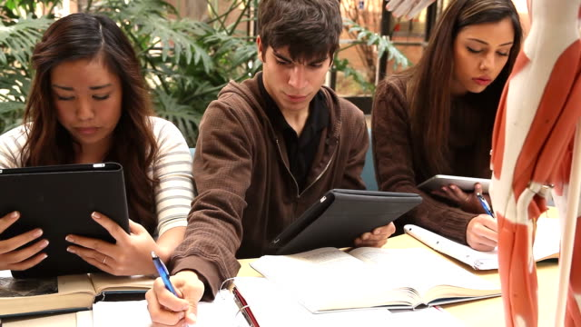 Three students using digital tablets to study video