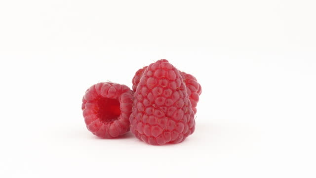 Three sweet juicy raspberry fruits on rotating table. Isolated, on white background. Healthy food concept