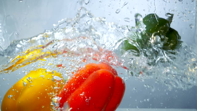 Three sweet peppers dive into clear water. A red, a yellow and a green pepper fall down inside clear water tank and make waves. paprika stock videos & royalty-free footage