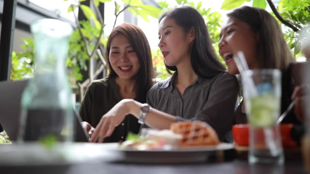 Three Taiwanese female friends using laptop on lunch break