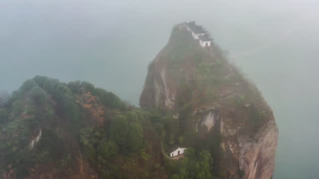 Three Taoist temples stand on the cliff island in the river