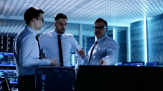 drei technische moderatoren haben eine aktive diskussion im überwachungsraum. der systemkontrollraum ist voll von working displays, die verschiedene daten zeigen und server racks haben. - it support stock-videos und b-roll-filmmaterial