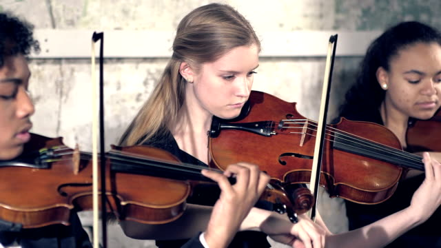 Three teenage violinists performing A group of three multi-ethnic teenager violinists performing in concert. The main focus is the 16 year old Caucasian girl in the middle. classical concert stock videos & royalty-free footage