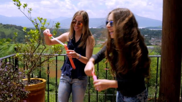 vídeos y material grabado en eventos de stock de tres jóvenes riendo y jugando fuera con burbujas en exclente - deportes de la escuela secundaria