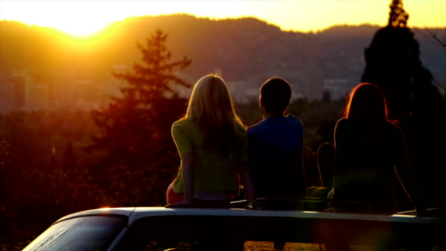 Three Teens Sit On Car And Watch The Sunset Together video