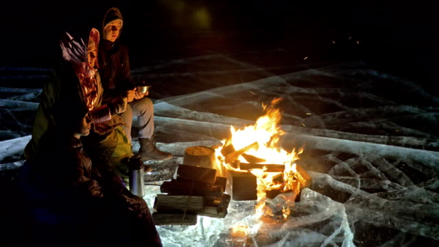 three travelers by fire right on ice at night. campground on ice. tent stands next to fire. lake baikal. nearby there is car. people are warming around campfire and are dressed in sleeping bags. - data scritta video stock e b–roll