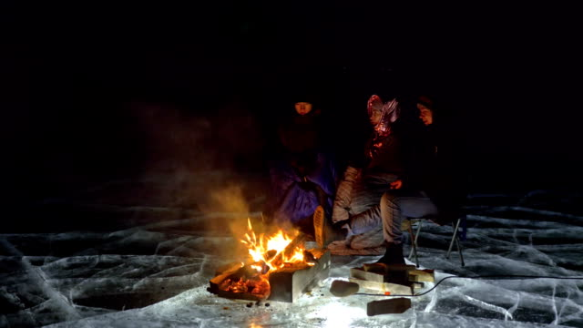 3 出張夜火災氷の上右による。氷の上のキャンプ場。テントは次に火に立っています。バイカル湖。近くには車です。人々 は、キャンプファイヤーの周りを暖めて、寝袋で服を着ています。 ビデオ