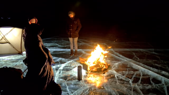 three travelers by fire right on ice at night. campground on ice. tent stands next to fire. lake baikal. nearby there is car. people are warming around campfire and are dressed in sleeping bags. - trekking sul ghiaccio video stock e b–roll
