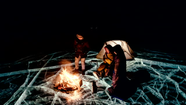 three travelers by the fire right on the ice at night. campground ice. the tent stands next to the fire. people are warming themselves by the fire. time-lapse with a circular motion. the lake baikal. - ice on fire video stock e b–roll