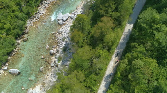 top down: three travelers ride bicycles along emerald soca river on a sunny day. - ghiaia video stock e b–roll