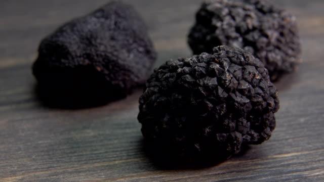 drei knollen von schwarzem trüffel auf dunklen holzfläche gelegt - knollig stock-videos und b-roll-filmmaterial